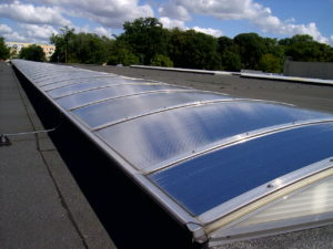 Pasmo świetlne inaczej świetlik dachowy z poliwęglanu pokryty folia przeciwsłoneczną.